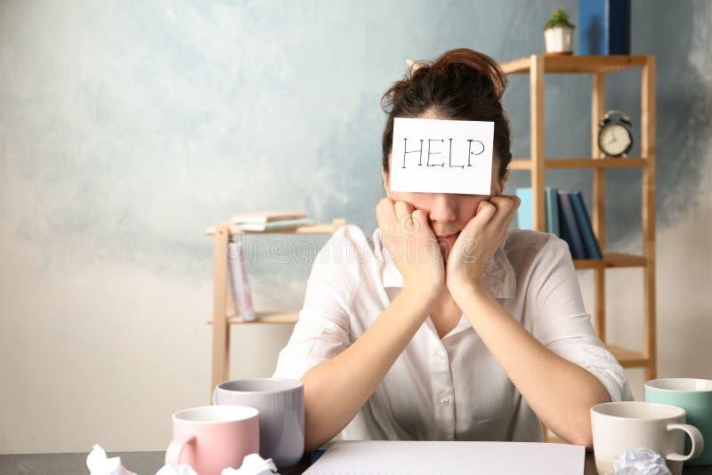Mujer joven con AYUDA de la nota en la frente en el lugar de trabajo fotografía de archivo