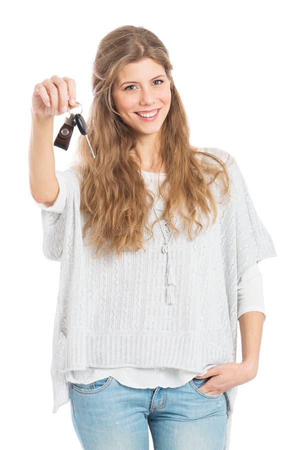 Mujer joven con clave del coche foto de archivo