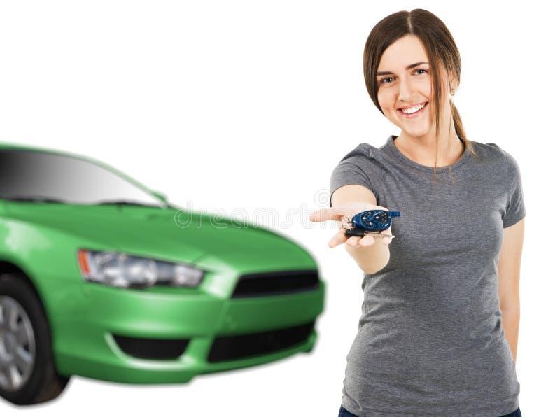 Mujer joven con claves del coche y el nuevo automóvil imagenes de archivo