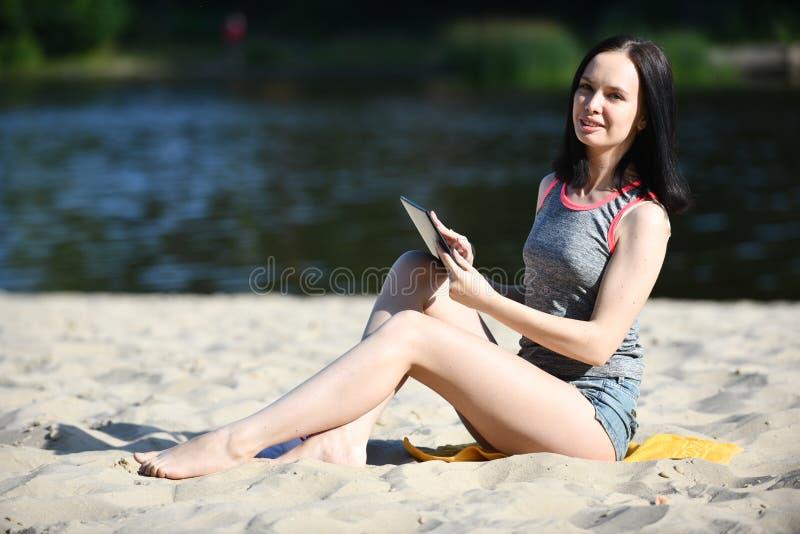 Mujer joven con el artilugio - tableta digital fotos de archivo
