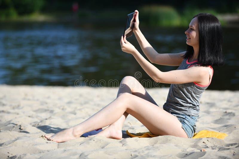 Mujer joven con el artilugio - tableta digital imagen de archivo