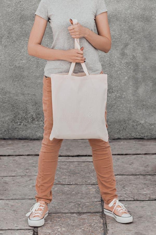 Mujer joven con el bolso blanco del algod?n en sus manos Mofa para arriba imagen de archivo