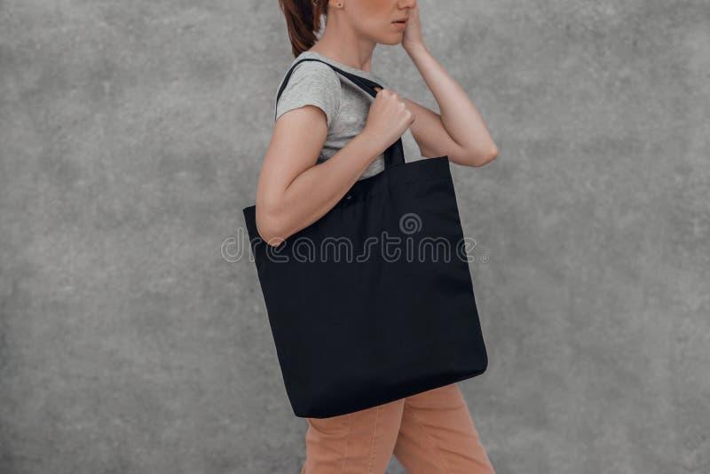 Mujer joven con el bolso negro del algodón en sus manos en fondo gris Mofa para arriba foto de archivo