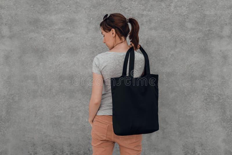 Mujer joven con el bolso negro del algodón en sus manos Mofa para arriba imagenes de archivo