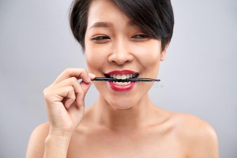 Mujer joven con el cepillo del labio fotografía de archivo