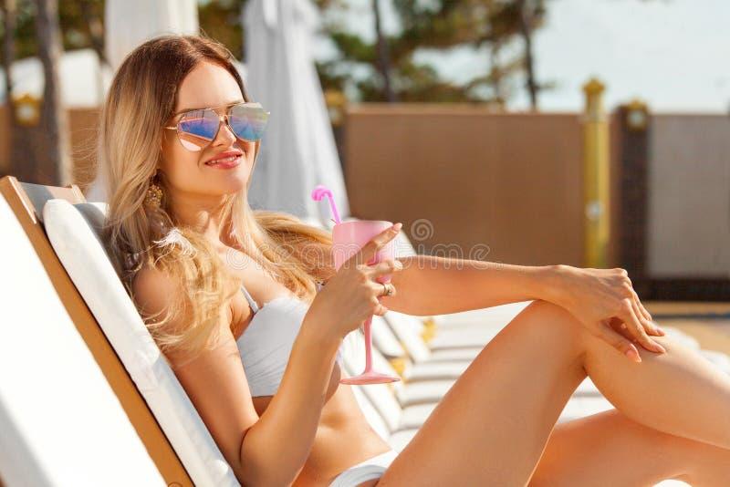 Mujer joven con el coctail en la playa en el verano fotografía de archivo