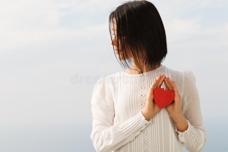 Mujer joven con el corazón de la tarjeta del día de San Valentín imagenes de archivo