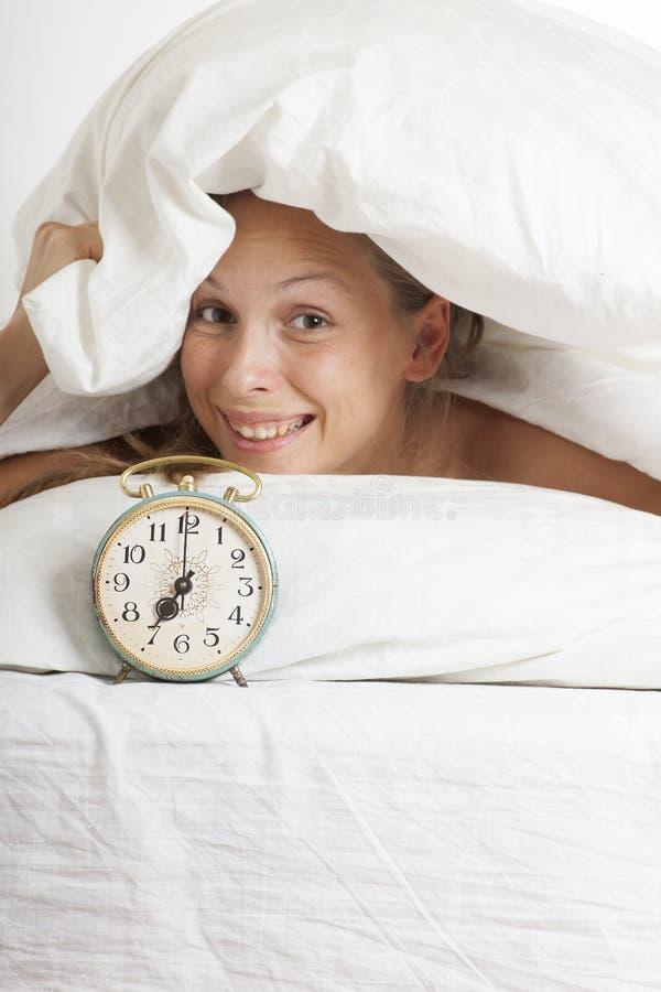 Mujer joven con el despertador en la cama en la mañana imagen de archivo libre de regalías