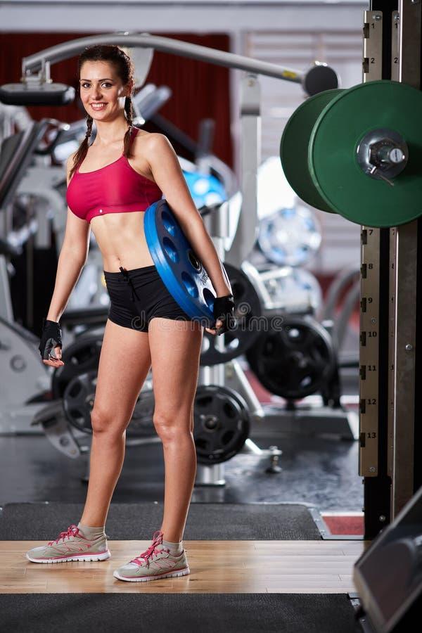 Mujer joven con el disco pesado en el gimnasio fotos de archivo