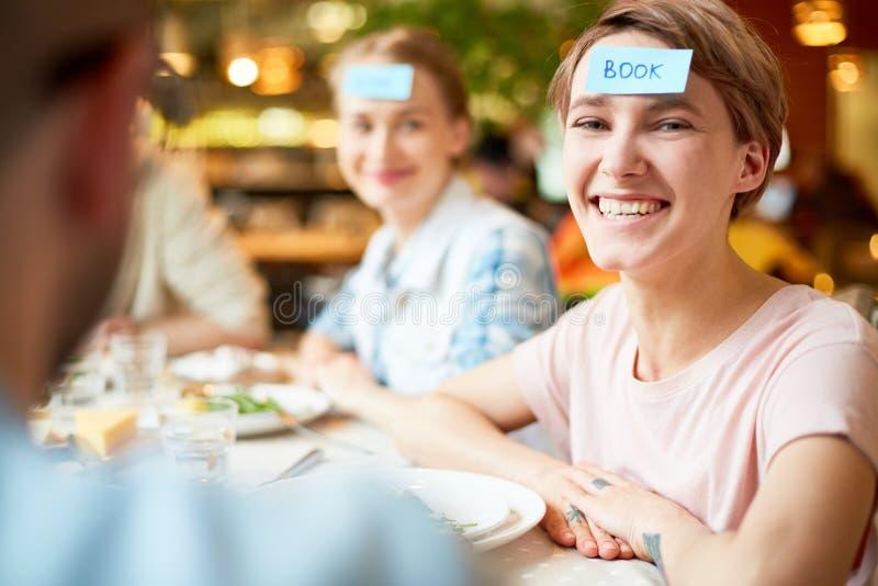 Mujer joven con el documento de pedazos sobre las frentes con los amigos en café imágenes de archivo libres de regalías