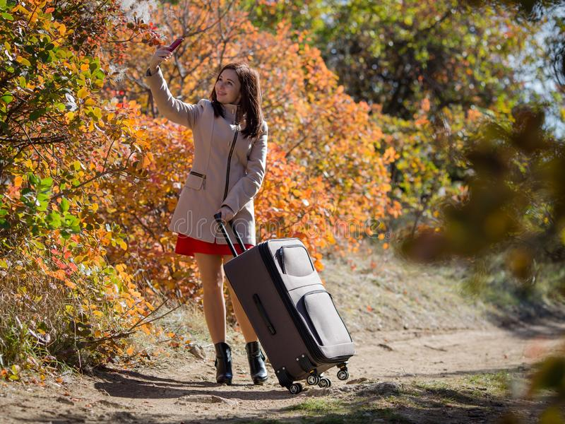 Mujer joven con el equipaje en la carretera nacional en la persona femenina del bosque en vestido rojo corto y la capa que toman  foto de archivo libre de regalías