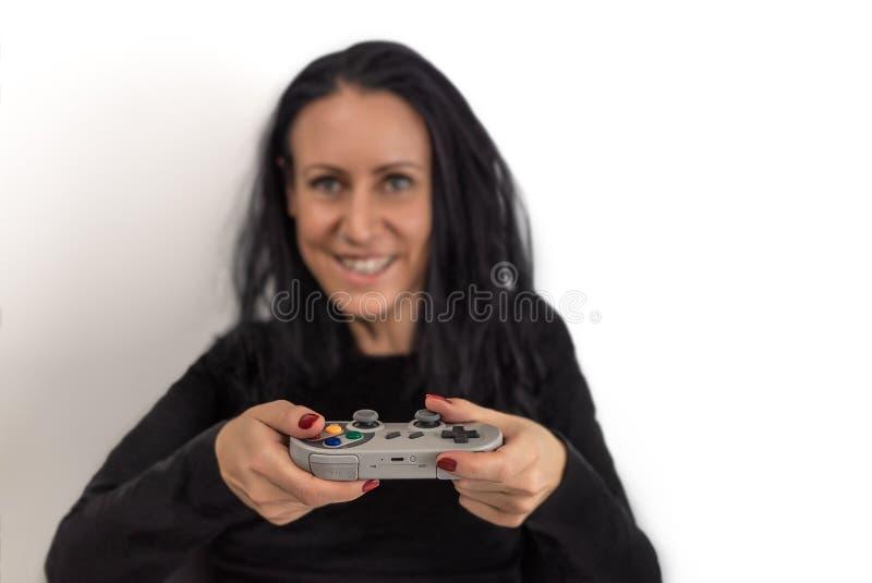 Mujer joven con el esmalte de uñas rojo que juega al videojuego en un regulador inalámbrico retro del juego con una expresión con imagenes de archivo