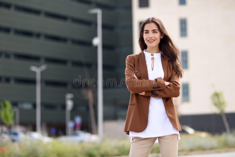 Mujer joven con el exterior derecho del pelo agradable del edificio de oficinas foto de archivo