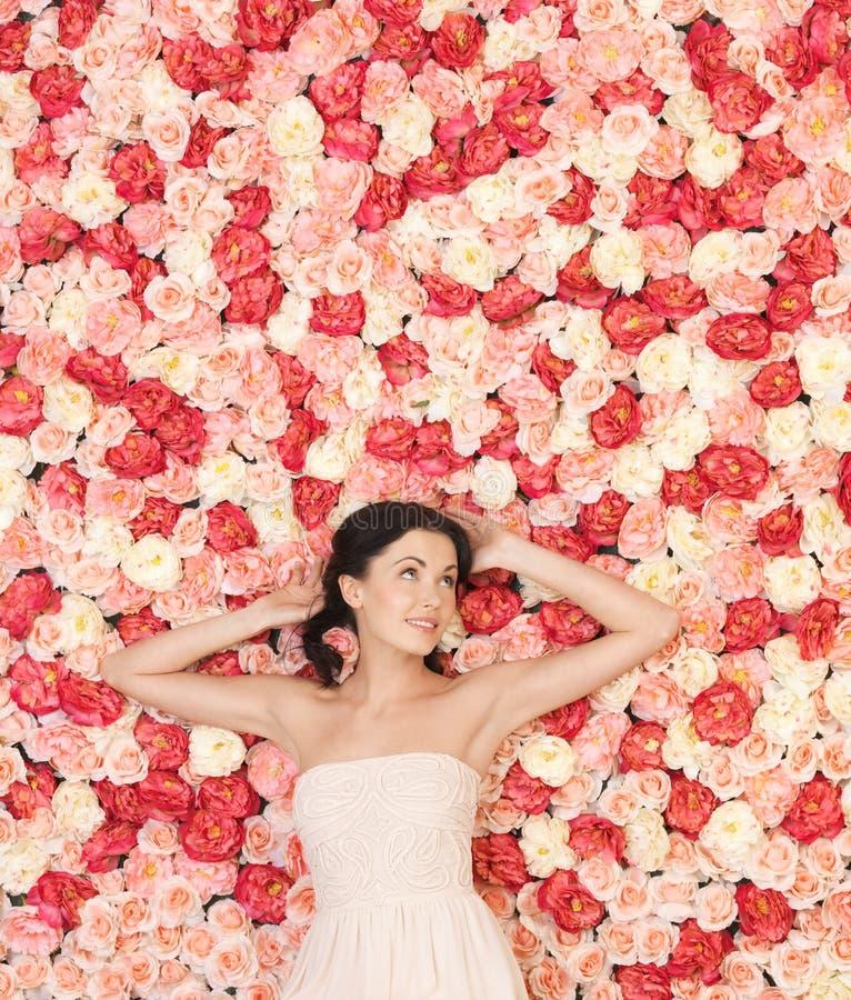 Mujer joven con el fondo lleno de rosas fotos de archivo libres de regalías
