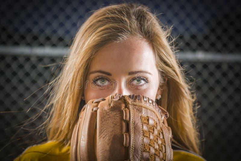 Mujer joven con el guante del softball que cubre su cara al aire libre foto de archivo libre de regalías