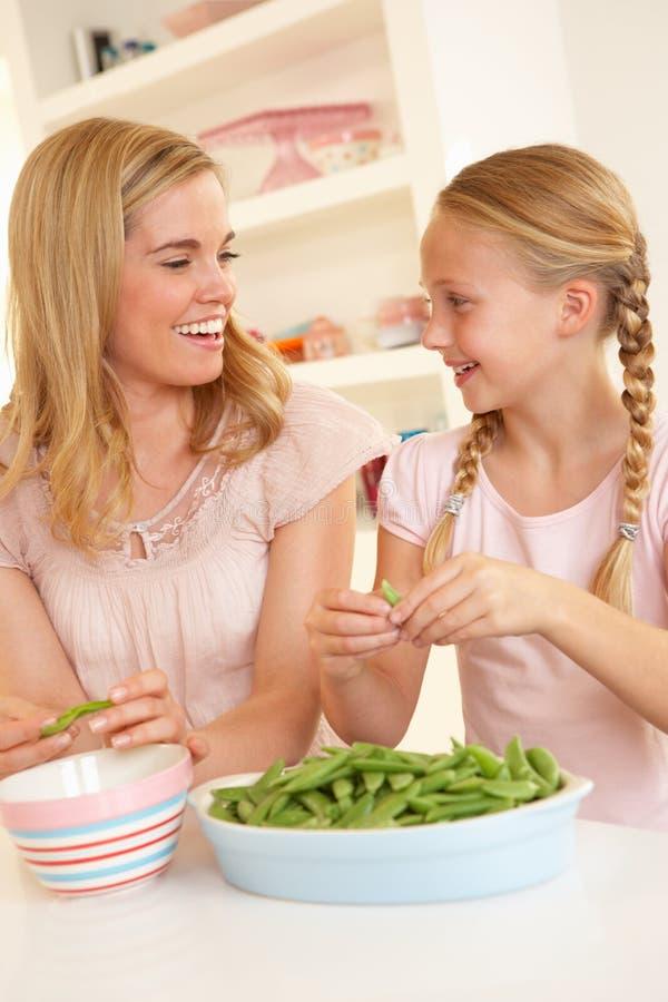 Mujer joven con el guisante que parte del niño en cocina fotografía de archivo