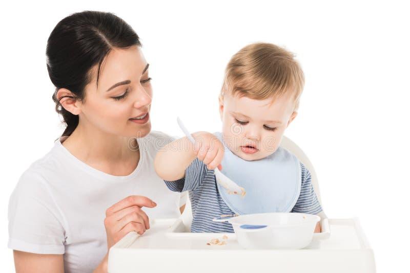 mujer joven con el hijo en highchair de consumición y que se sienta del babero imagen de archivo