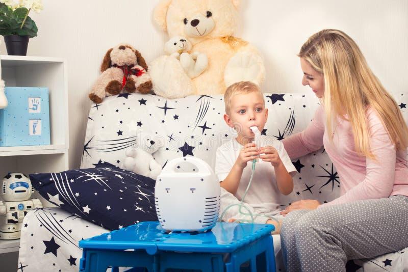 Mujer joven con el hijo que hace la inhalación con un nebulizador en casa imagenes de archivo