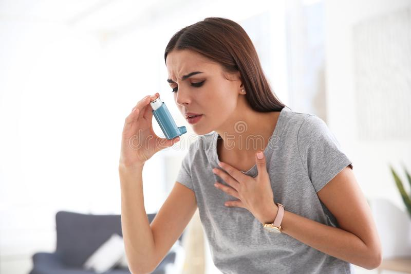 Mujer joven con el inhalador del asma imagenes de archivo