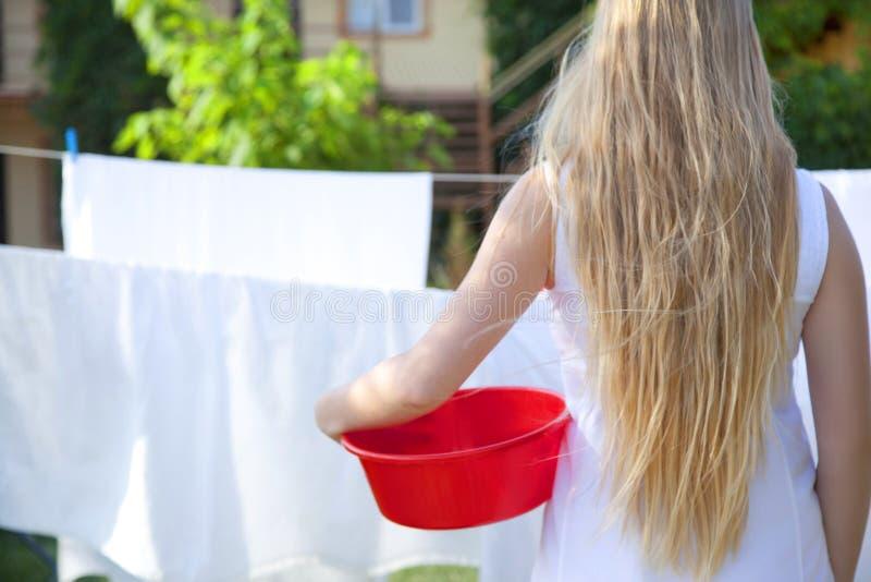 Mujer joven con el lavabo en manos Situación adolescente de la muchacha cerca de las hojas imagenes de archivo