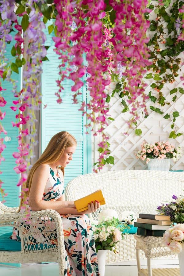 Mujer joven con el libro en terraza del verano foto de archivo libre de regalías