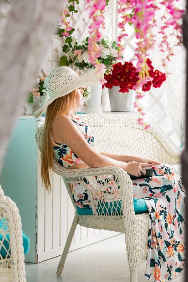 Mujer joven con el libro en terraza del verano imagenes de archivo