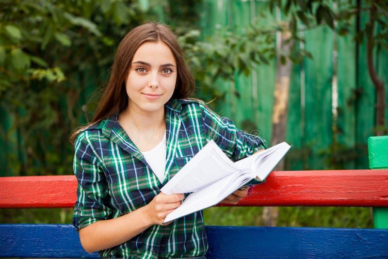 Mujer joven con el libro que mira en la cámara fotografía de archivo