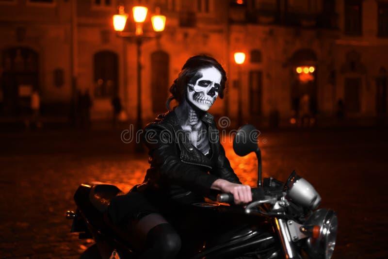 Mujer joven con el maquillaje de Halloween que se sienta en la moto Retrato de la calle foto de archivo