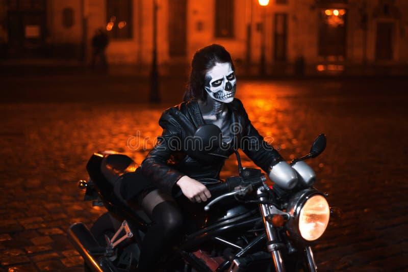 Mujer joven con el maquillaje de Halloween que se sienta en la moto Retrato de la calle imágenes de archivo libres de regalías