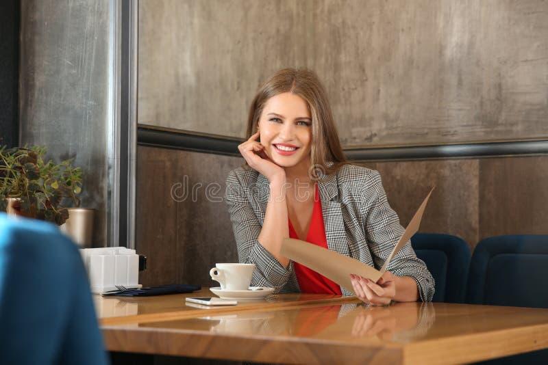 Mujer joven con el menú que se sienta en restaurante fotografía de archivo