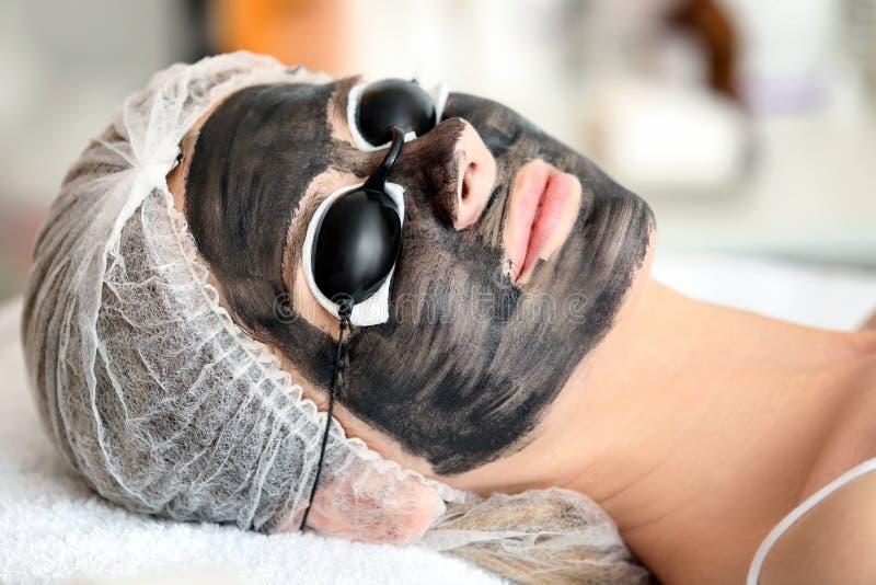 Mujer joven con el nanogel del carbono en su cara en salón imágenes de archivo libres de regalías