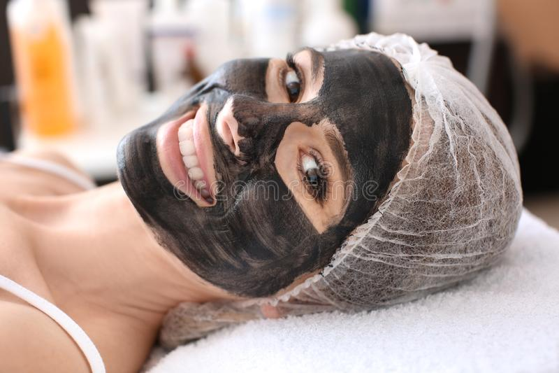 Mujer joven con el nanogel del carbono en su cara en salón foto de archivo