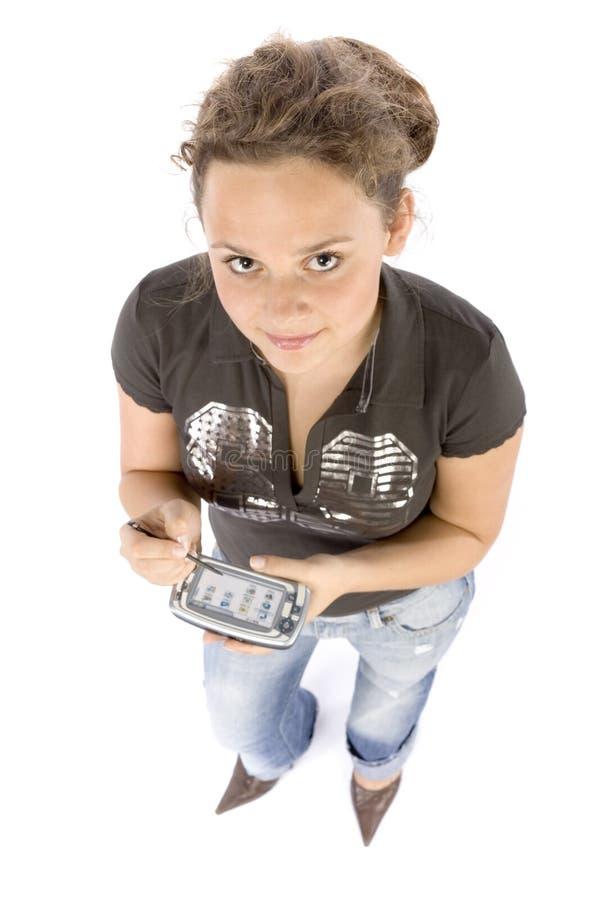 Mujer joven con el ordenador del bolsillo o el teléfono móvil fotos de archivo