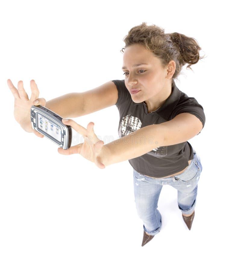 Mujer joven con el ordenador del bolsillo o el teléfono móvil fotografía de archivo