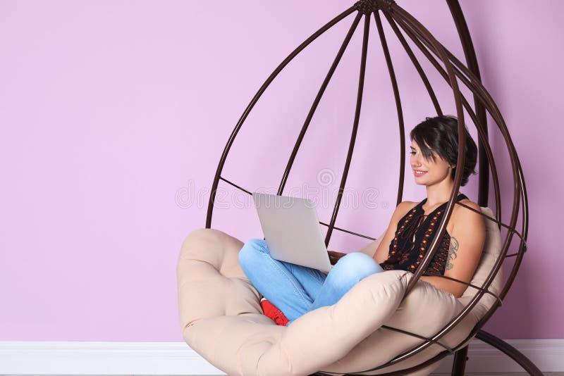 Mujer joven con el ordenador portátil moderno que se sienta en silla de la ejecución fotografía de archivo libre de regalías