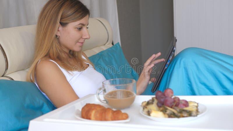 Mujer joven con el ordenador portátil que come el desayuno en cama en casa y que bebe el café foto de archivo libre de regalías
