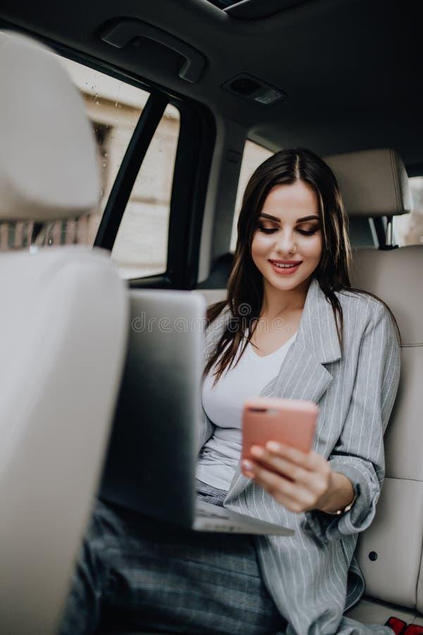 Mujer joven con el ordenador portátil que se sienta en coche y que habla en el teléfono fotos de archivo libres de regalías