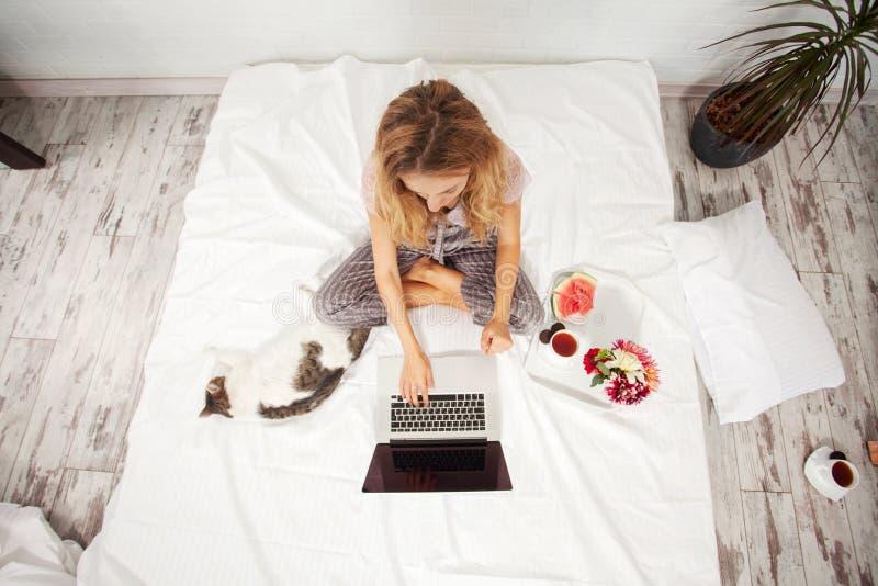 Mujer joven con el ordenador port?til en la cama imágenes de archivo libres de regalías