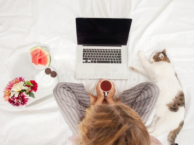 Mujer joven con el ordenador port?til en la cama fotografía de archivo libre de regalías