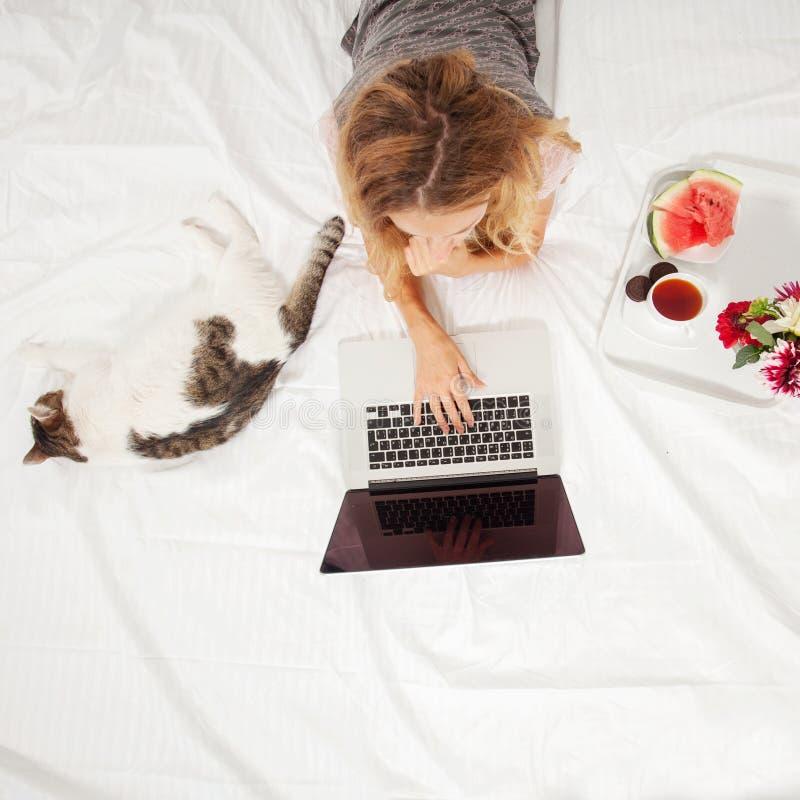 Mujer joven con el ordenador port?til en la cama foto de archivo