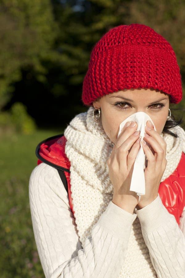 Mujer joven con el pañuelo y la gripe imagen de archivo libre de regalías