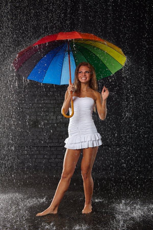 Mujer joven con el paraguas multicolor foto de archivo