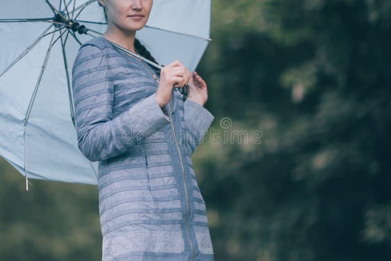Mujer joven con el paraguas que se coloca en la trayectoria en el parque fotos de archivo