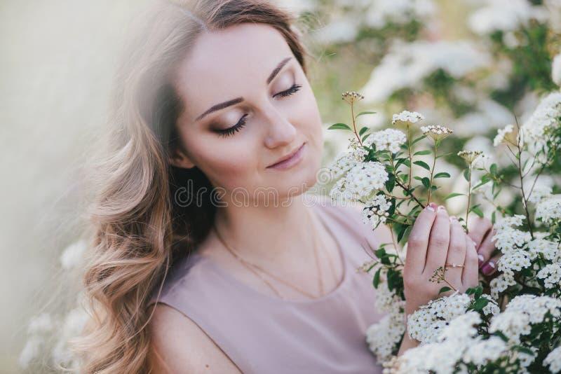 Mujer joven con el pelo hermoso largo en un vestido de la gasa que presenta con el jardín del lilacin con las flores blancas imagenes de archivo