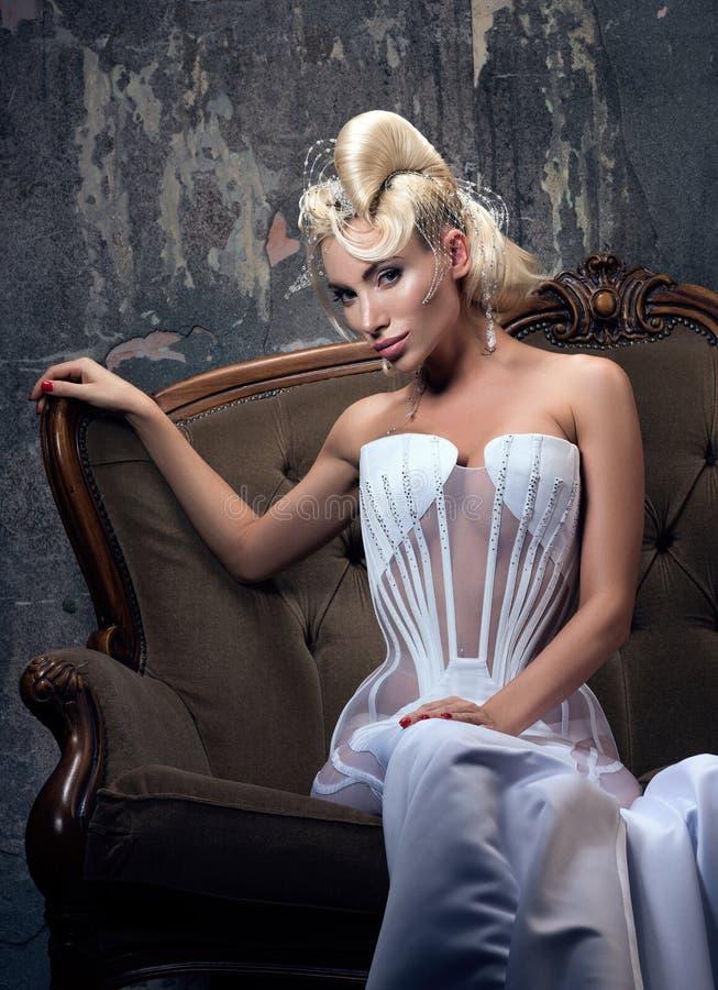 Mujer joven con el pelo hermoso y la mirada sensual que se sientan en un sofá del vintage imágenes de archivo libres de regalías