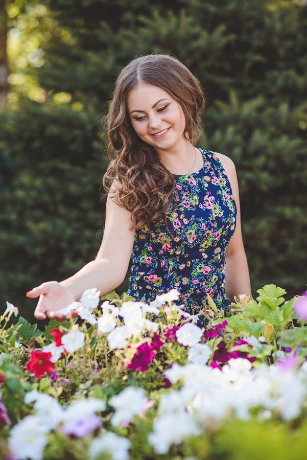 Mujer joven con el pelo largo hermoso en vestido de flores cerca de los carros de madera decorativos con las flores, en un fondo  imagenes de archivo