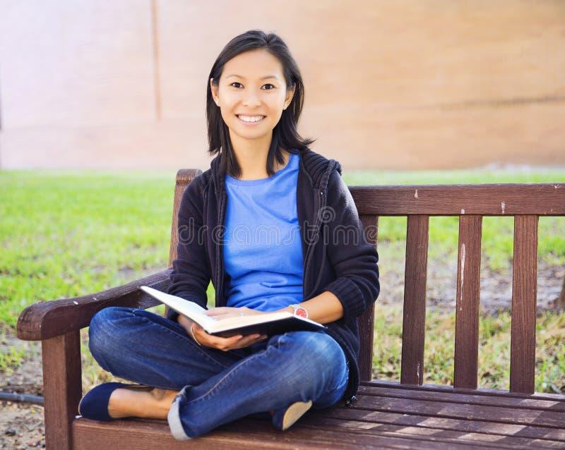 Mujer joven con el pelo largo que se sienta en la lectura del asiento de ventana foto de archivo libre de regalías