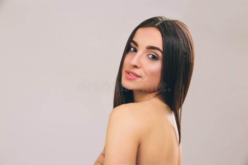 Mujer joven con el pelo negro largo que presenta en c?mara El parecer recto y sonrisa Pelo liso Modelo hermoso aislado encendido fotografía de archivo
