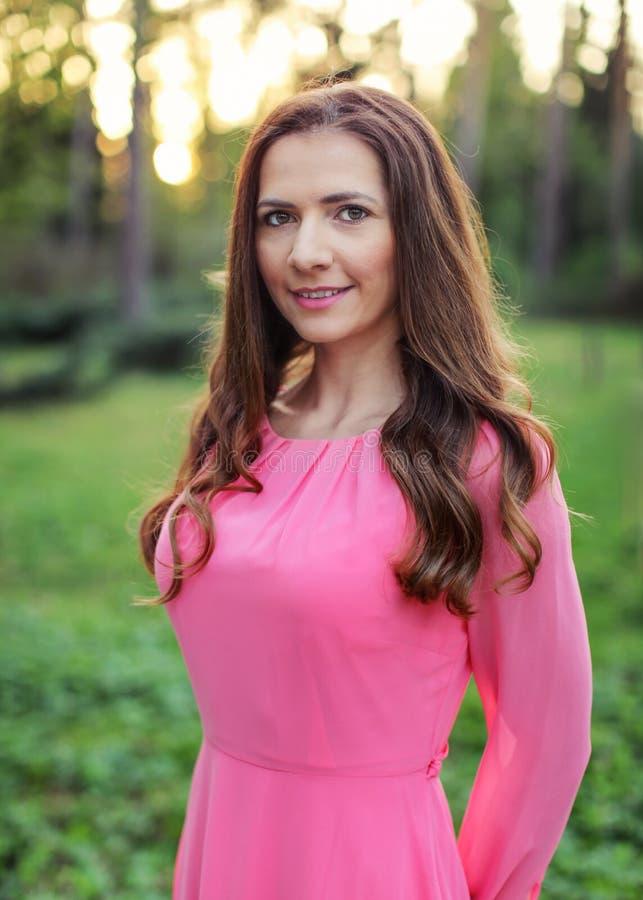 Mujer joven con el pelo oscuro largo, vestido rosado que lleva, photographe imagen de archivo
