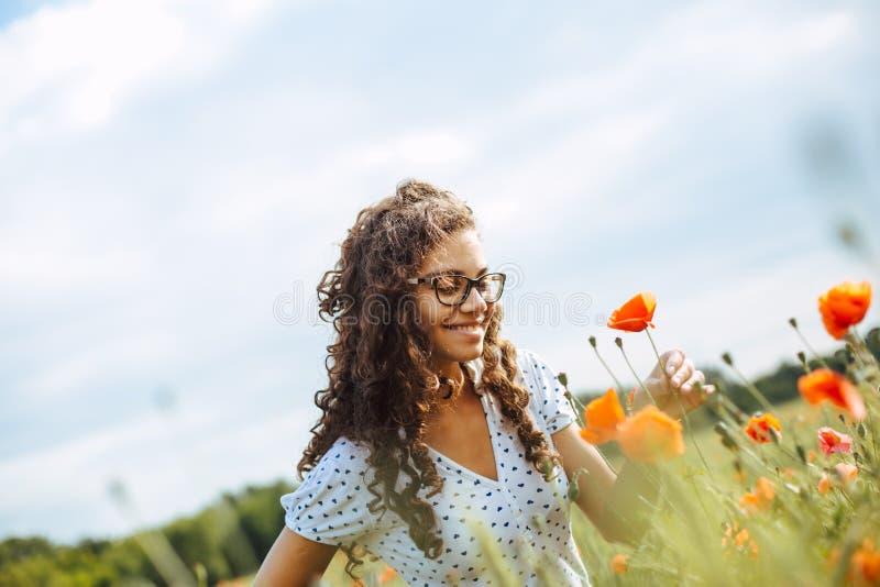 Mujer joven con el pelo rizado en un campo de flores salvajes imagenes de archivo